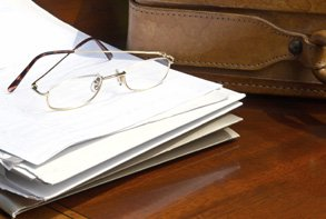 a pair of reading glasses on top of a pile documents, next to a brown leather briefcase
